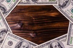 Frame of one hundred dollars bills on wooden table. Top view. Frame of the one hundred dollars bills on rustic wooden table. Top view Stock Image