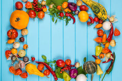 Frame of organic vegetables on blue wooden background. Organic food concept. Space for text. Royalty Free Stock Photography