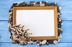 Frame of pebbles and shells on a blue wooden background royalty free stock photo