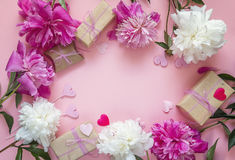 Frame of peonies, gift boxes and decorative hearts on a pink bac Royalty Free Stock Images