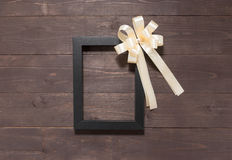 Frame picture and ribbon are on the wooden background with empty Stock Photo