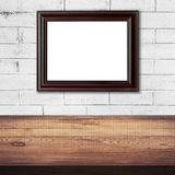 Frame picture on white brick wall and wood table background Stock Images