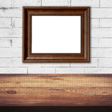 Frame picture on white brick wall and wood table background royalty free stock photography