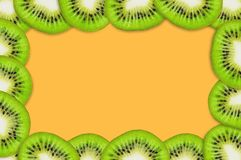 Frame with pieces of sliced tasty beautiful ripe fresh kiwi fruit on orange table in kitchen. Top view. Cooking concept. Copy space for your text royalty free stock images