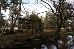 The frame of pine trees, statue, and shrine at Kenrokuen Garden royalty free stock photos