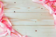 Frame of pink ribbons on natural wooden background with copy space. Mock up for text, for phrases, for lettering, for congratulations Stock Images