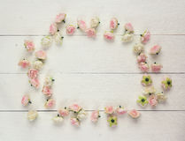 Frame of pink small roses on a white wooden background with empt. Y space for text. Top view Stock Photos