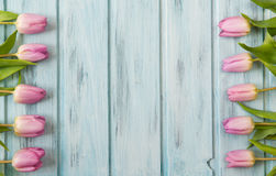 Frame with pink tulip flowers and wooden background, copy space Stock Image