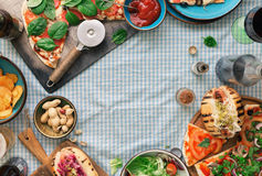 Frame of pizza, hot dog, salad, wine, lager, snacks. Frame of Italian pizza, hot dog grilled, salad, red wine, lager and snacks to beer, top view. Dinner table stock image