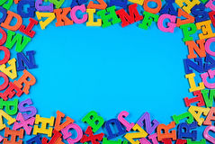 Frame of plastic colorful alphabet letters on a blue Royalty Free Stock Photos
