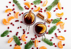 Frame of pomegranate seeds, mandarines and twigs tree with two. Glasses of hot mulled wine with oranges and spices. Xmas handmade decoration on white table royalty free stock images