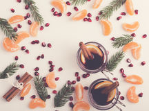 Frame of pomegranate seeds, mandarines and twigs tree with two. Glasses of hot mulled wine with oranges and spices. Xmas handmade decoration on white table royalty free stock photography