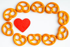 Frame of pretzels and red heart white background Stock Photography