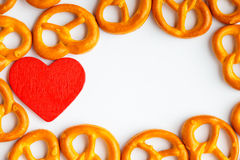 Frame of pretzels and red heart white background Stock Photos