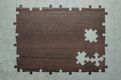 Frame of puzzle pieces on wooden background Stock Photo