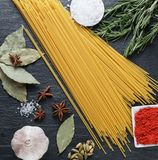 Raw food ingredients for preparing pasta. Frame with raw ingredients for pasta cooking at home - spagetti, spices, salt,pepper, high angle view Royalty Free Stock Image