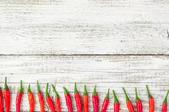 Frame of red Chile pepper on white wooden table.  Royalty Free Stock Images