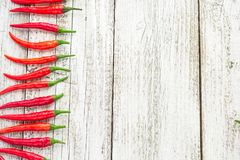 Frame of red Chile pepper on white wooden table.  Royalty Free Stock Photo