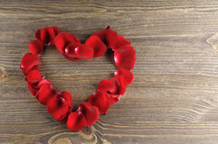 Frame of red rose petals heart on a wood background. Stock Images