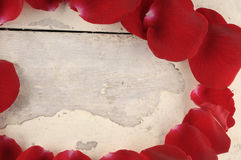 Frame of red rose petals on a wood background. Royalty Free Stock Images