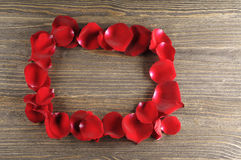 Frame of red rose petals on a wood background. Stock Images