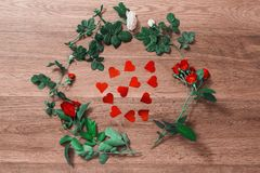 Frame of red roses with green leaves and red hearts on a wooden background Royalty Free Stock Images