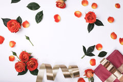Frame with red roses, red gift box and gold ribbon Stock Photo