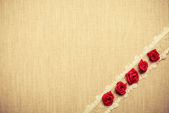 Frame of red silk roses on cloth Stock Image