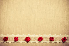Frame of red silk roses on cloth Stock Photo