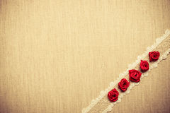 Frame of red silk roses on cloth Stock Photography