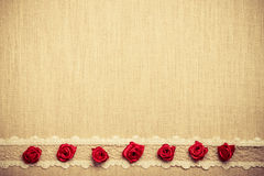 Frame of red silk roses on cloth Royalty Free Stock Images