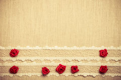 Frame of red silk roses on cloth Stock Images
