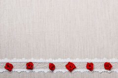 Frame of red silk roses on cloth Royalty Free Stock Photos