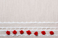Frame of red silk roses on cloth Royalty Free Stock Photo