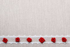 Frame of red silk roses on cloth Stock Photos