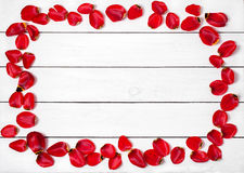 Frame of red tulip petals on a wooden table Stock Photo