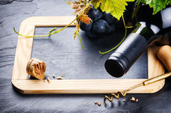 Frame with red wine bottle and fresh grape Royalty Free Stock Photo