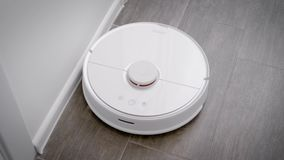 In the frame is a robot vacuum cleaner that cleans the floor in the kitchen. stock footage