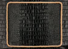 Frame of rope, lies on a background of a black crocodile  leathe Royalty Free Stock Image