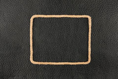 Frame of rope, lies on a background of a black natural leather Royalty Free Stock Photo