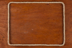 Frame of rope, lies on a background of a wooden surface Royalty Free Stock Photo