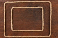 Frame of rope, lies on a background of a wooden surface Stock Image