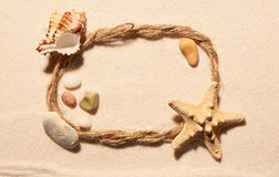 Frame of rope with starfish, seashell and stones on sand Stock Photo
