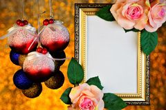 Frame of rose flowers and Christmas toy balls on romantic festive gold background of bokeh lights. Frame for photo, picture or important text, colorful stock image