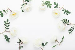 Frame of rose flowers and green leaves on white table top view. Beautiful wedding pattern in flat lay styling. stock images