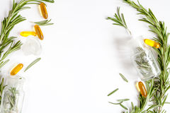 Frame from rosemary, bottles, pills on white background top view Stock Image