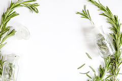 Frame from rosemary, bottles on white background top view Royalty Free Stock Photography
