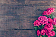 Frame of roses on dark rustic wooden background. Spring flowers. Royalty Free Stock Image