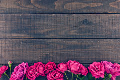 Frame of roses on dark rustic wooden background. Spring flowers. Spring background. Valentine's Day and Mother's Day background. Holiday mock up. Top view Royalty Free Stock Images