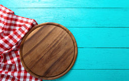 Frame of round cutting board and red plaid tablecloth. Blue wooden background in the cafe. Top view Stock Images